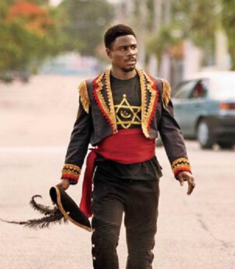 馬爾尚戴維斯飾演邁阿密小地區的黑人領袖「摩西」,是聲量龐大的國家革命者,卻堅信和平主義,造反國家竟不用槍枝,而是聲稱吹號角就能「召喚恐龍」。(圖/車庫電影提供)