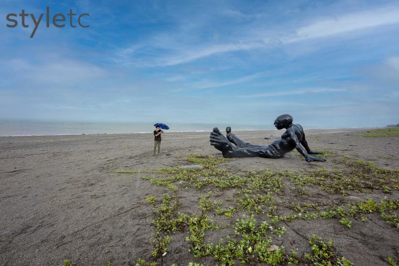 赤腳大足的黑色巨人《行走的意識》,面向大海坐臥在沙灘上。(圖/焦正德攝)