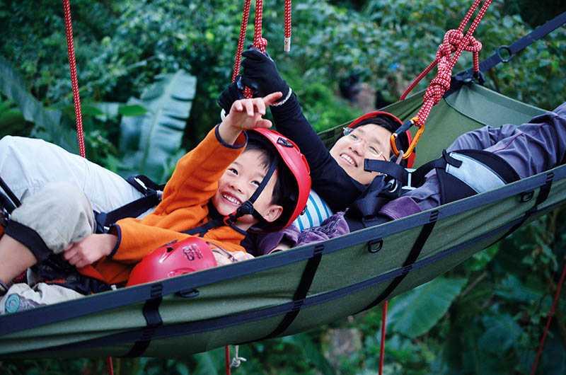 體驗攀樹的大人與小孩,在枝條間遊走累了,可躺在吊床上野餐及休憩。(圖/攀樹趣提供)