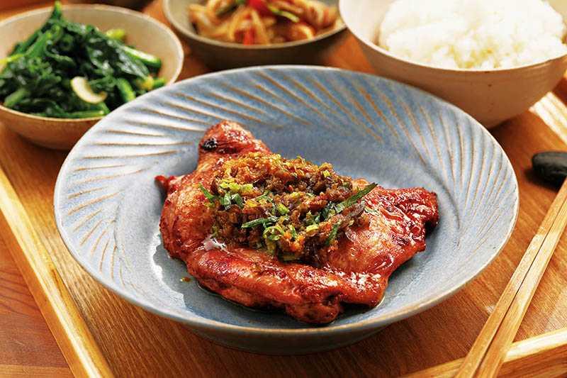 「紅糟酒粕烤雞」先用來自馬祖媽媽釀的紅糟醃製一晚,煎烤後淋上一層剝皮辣椒與油蔥拌炒的特調醬料,滋味濃郁馨香。(390元/套餐)(圖/于魯光)