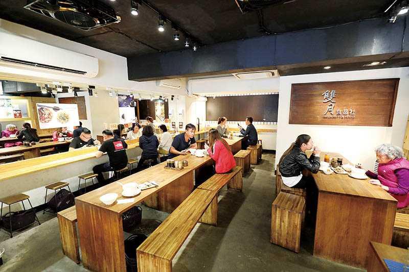 「雙月食品社」使用木質長桌與長凳,增添空間流暢感。(圖/于魯光攝)