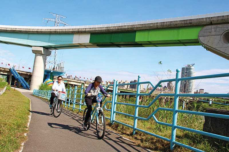 在攝影族喜歡取景的新店溪高架軌道下,騎車追捷運、賞河景,別有一番樂趣。(圖/楊麗雯攝影)