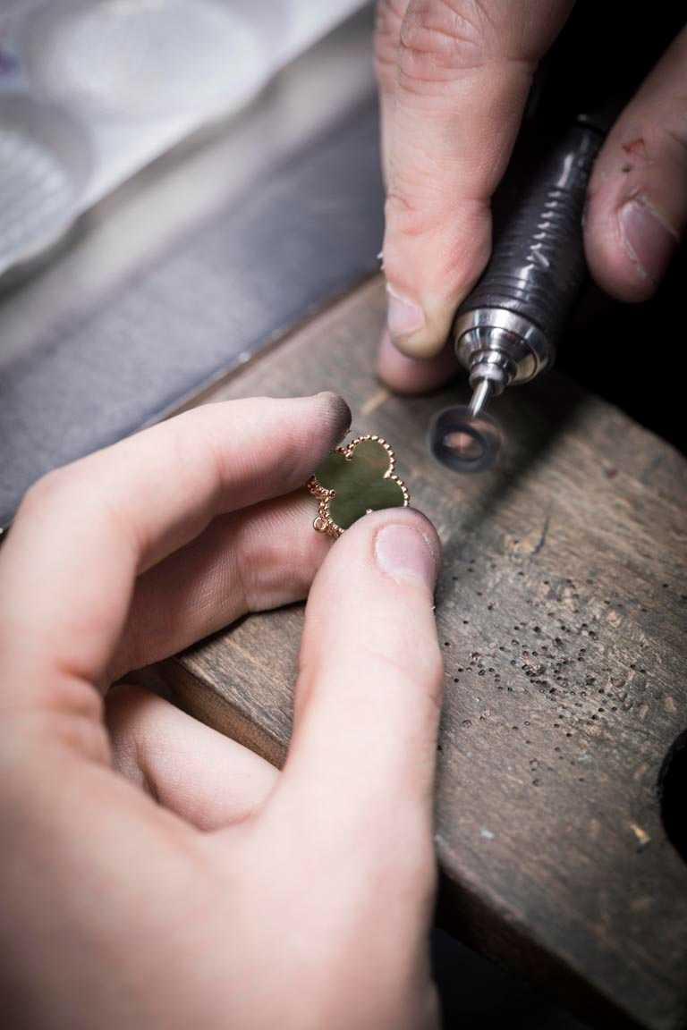 Van Cleef & Arpels大師級珠寶工匠,悉心拋光潤飾金色圓珠飾邊。(圖╱Van Cleef & Arpels提供)