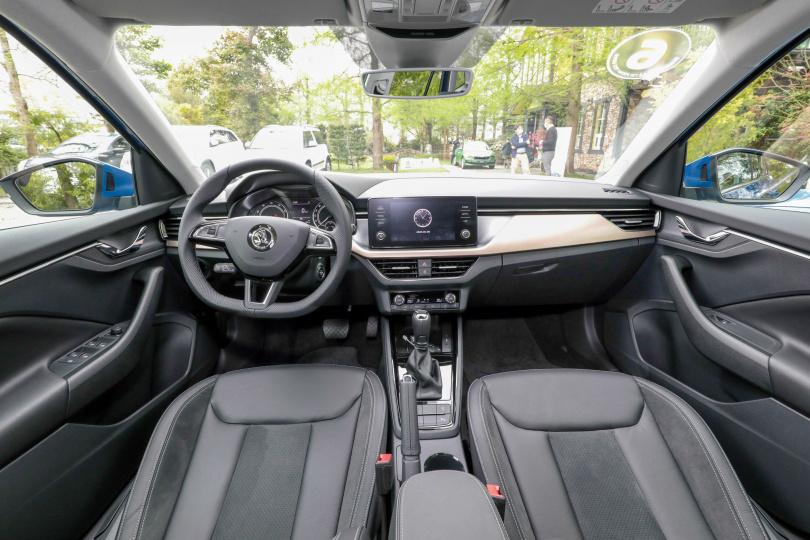 車室空間大量採用軟材質,副駕駛座前的飾板帶有木質感。(圖/馬景平攝)
