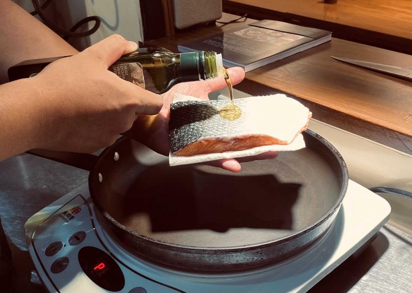 3.以中小火預熱不沾平底鍋,在魚皮上倒少許橄欖油抹勻,再將魚皮朝下放入平底鍋油煎。等到魚肉稍微縮起來,用掌心部分輕輕且溫柔地把魚肉往下壓,直到魚肉往下舒緩變平後,在魚肉上撒點香料鹽。