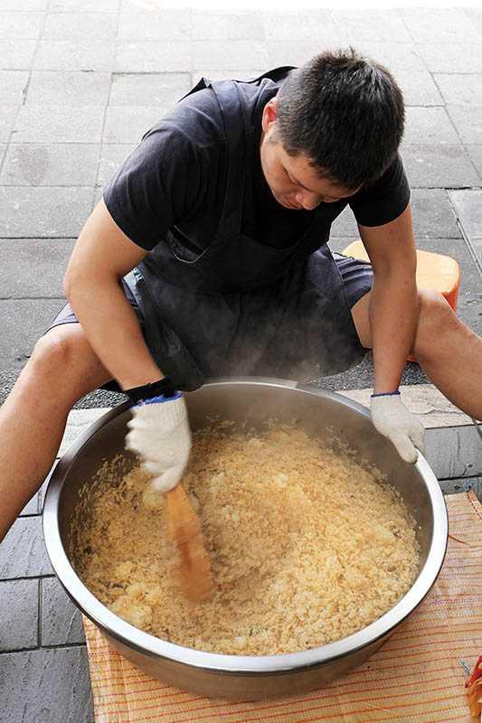 目前拌油飯是老闆兒子的工作,需使勁用力攪拌,讓糯米和醬汁混合均勻。(圖/于魯光)