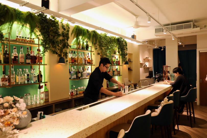 酒牆上的三座木拱門以湖水綠襯底,搭配玫瑰金屬吊櫃,讓「Messier 87 bar」帶有低調的奢華感。