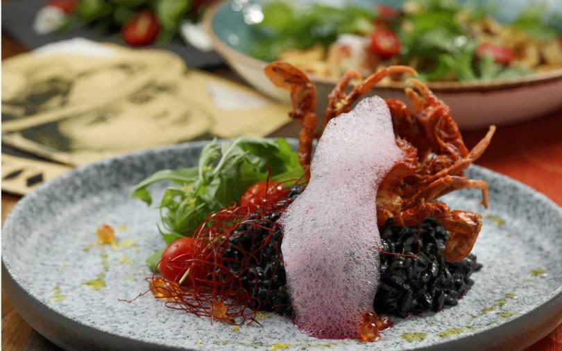 「酥炸軟殼蟹墨汁燉飯」裹上香料粉酥炸的軟殼蟹,與墨汁燉飯的搭配充滿濃郁海味(420元)。(圖/于魯光攝)