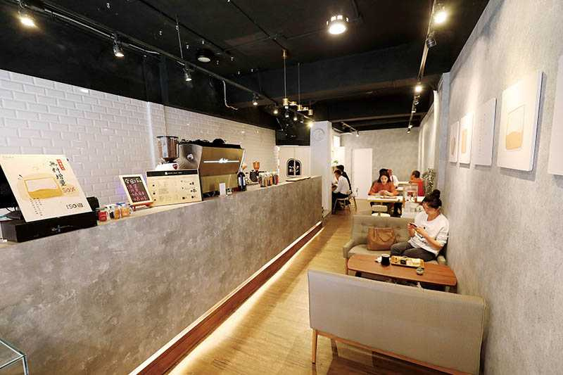 狹長型店面有單人座也有沙發區,水泥牆面與木桌白椅風格十分清新。(圖/于魯光攝)