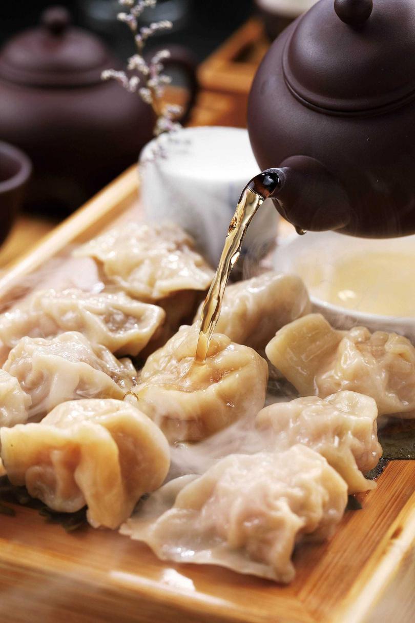 享用「穀雨觀音煮水餃」前,先將茶湯淋上黑山嫩豚水餃,清新茶香使人解膩。(230元)(圖/于魯光攝)