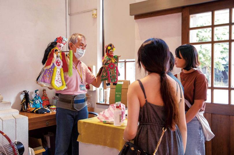 現場志工親自示範布袋戲偶,並一一說明獨特造型美學。(圖/宋岱融攝)