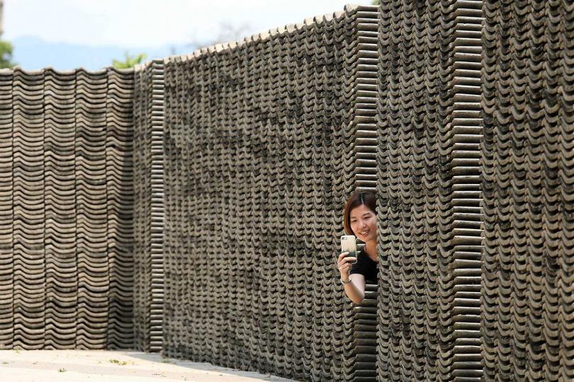 館內後方的牆,用屋頂拆卸下來的水泥瓦片堆疊而成,具有現代極簡風格。(圖/于魯光攝)