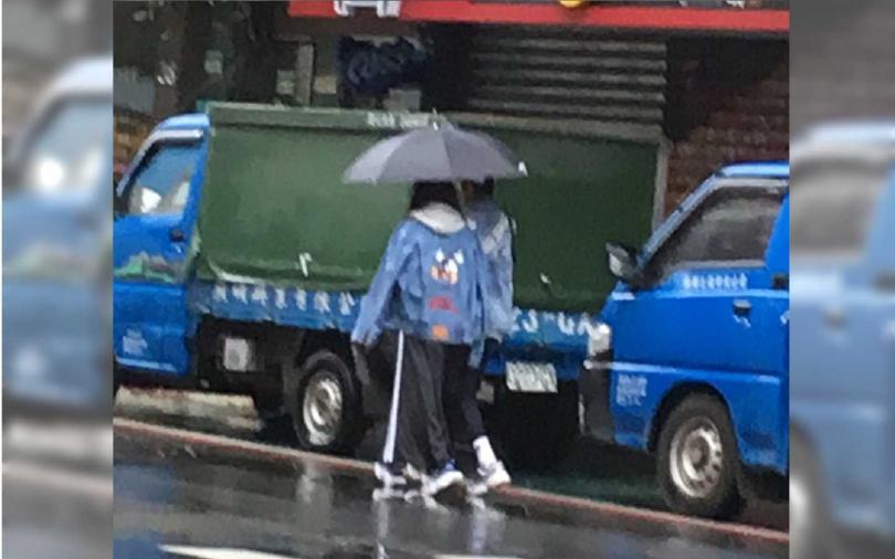 不讓老婆為他撐傘,阿翔主動為老婆擋雨,兩人依偎在傘下,畫面浪漫。(圖/本刊攝影組)