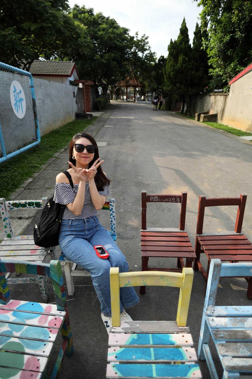 園區門口擺放著經過彩繪的小學生木椅,頗有童趣。(圖/于魯光攝)