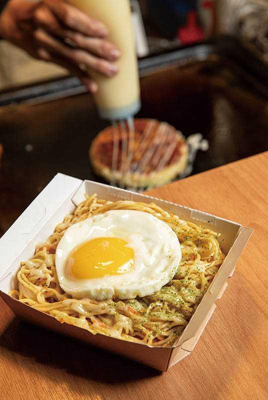 「日式炒麵」盛盒後,還會加一顆半熟荷包蛋,蛋黃戳破後拌入麵中,香氣又多一重(60元)。(圖/宋岱融攝)