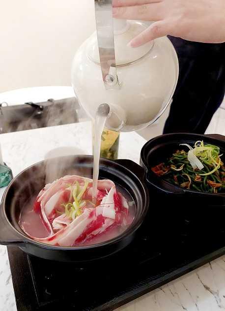 「鮮燙玫瑰牛湯/古早味蒜香乾拌麵」沖入的高湯使用牛大骨加蔬菜熬煮,可以先嘗原味,再加有放藥材的料酒進去。(圖/魏妤靜攝)