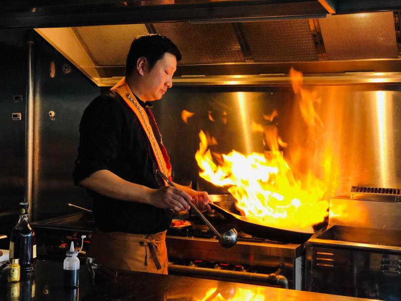 烹調鵝肝與和牛的過程中,主廚加入威士忌點火激出香氣。(圖/余玫鈴攝)