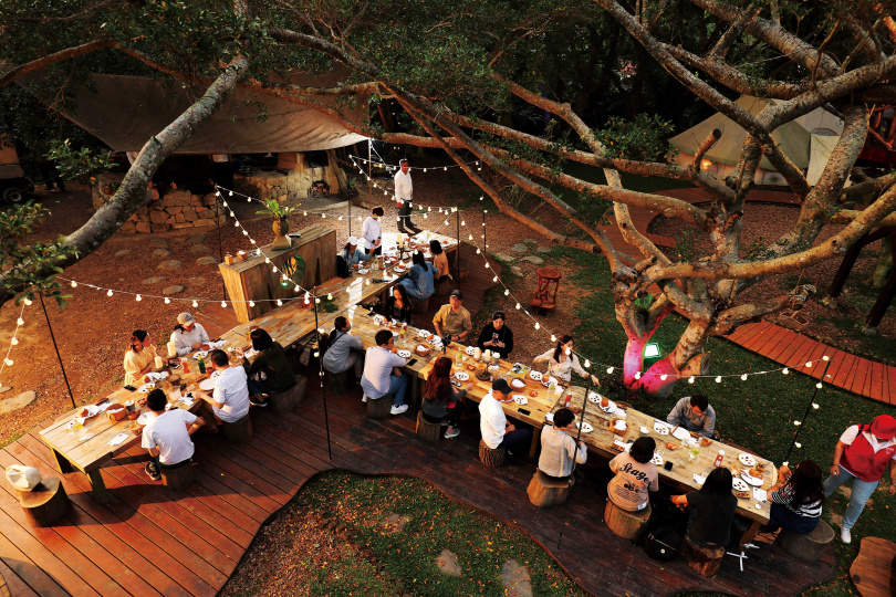 由多種木材拼接而成的長板桌,宛如巨人的雙手,端上豐盛的「獵人晚餐」,迎接旅人。(圖/于魯光攝)