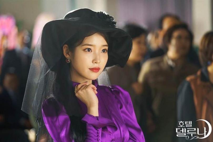 這一身高雅紫的絲緞長洋裝搭配黑色寬沿帽反而帥得不得了!/《德魯納酒店》官方劇照