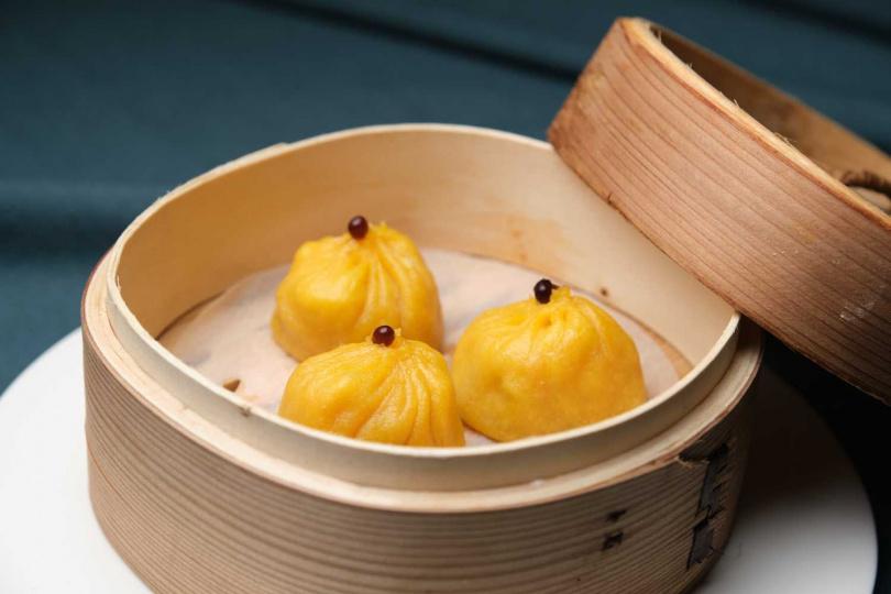 蟹黃小籠包內餡以蟹黃醬和手剝蟹肉絲,餡香湯鮮。(圖/玖尹餐酒館提供)