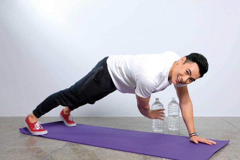 經營健身房副業的陸羿,示範在家就能進行的「平板撐」等基礎運動。(攝影/施岳呈)
