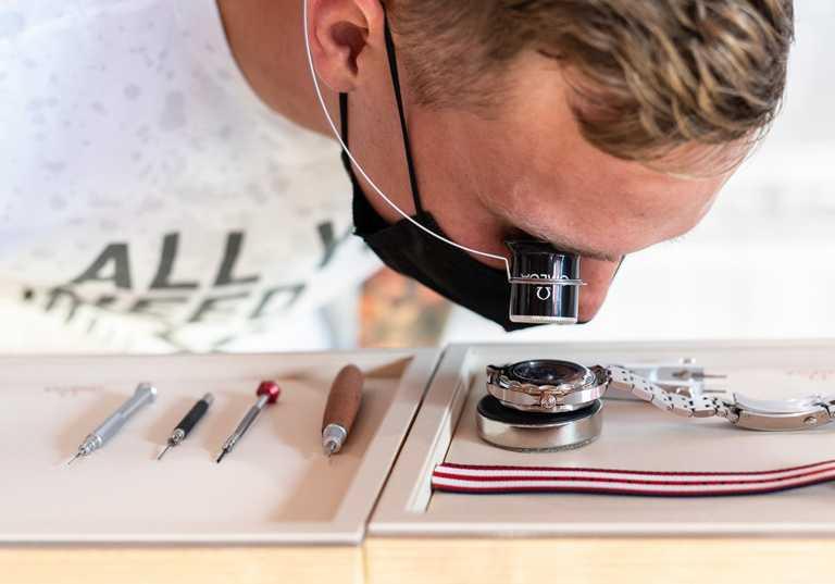 德萊賽爾透過放大鏡欣賞機芯的運行美態,精準感受勝負關鍵的微小分秒差距。(圖╱OMEGA提供)