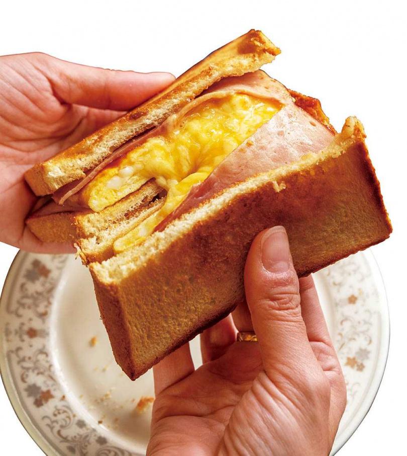 熱騰騰的「火腿起司蛋鐵板吐司」一切開的牽絲起司,勾人食慾。(35元)(圖/焦正德攝)