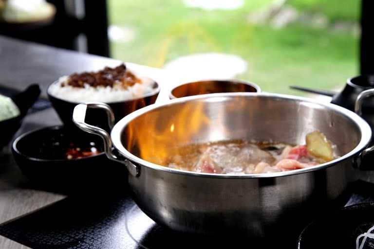 「爆炒燒酒蛤蜊雞」,先以麻油、老薑、土雞肉爆炒,中段再加入約大量米酒點火燃燒,逼出香氣後再加入高湯,香氣四溢。(379元)