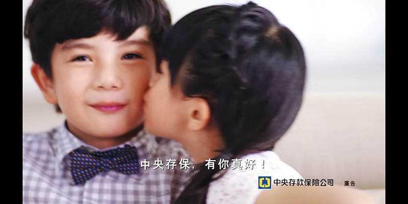 小二時吳以涵與另一名童星拍攝「中央存保」廣告,親親這一幕讓不少男同學吃醋。(圖/翻攝自YOUTUBE)