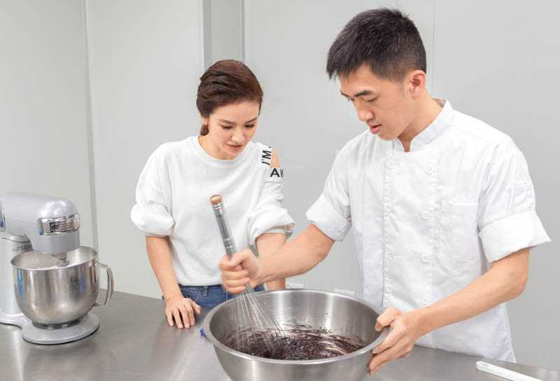攪拌麵糊的步驟最容易出錯,在阿豪師傅示範下,陳小菁學到不少烘焙技巧。(圖/林勝發攝)