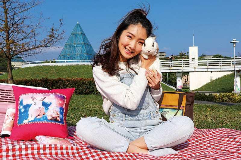 卡內外表呆萌,看不出已是10歲的「兔瑞」,採訪當天,許瀞蔆抱著牠和印有牠畫像的抱枕合照。(圖/焦正德攝)
