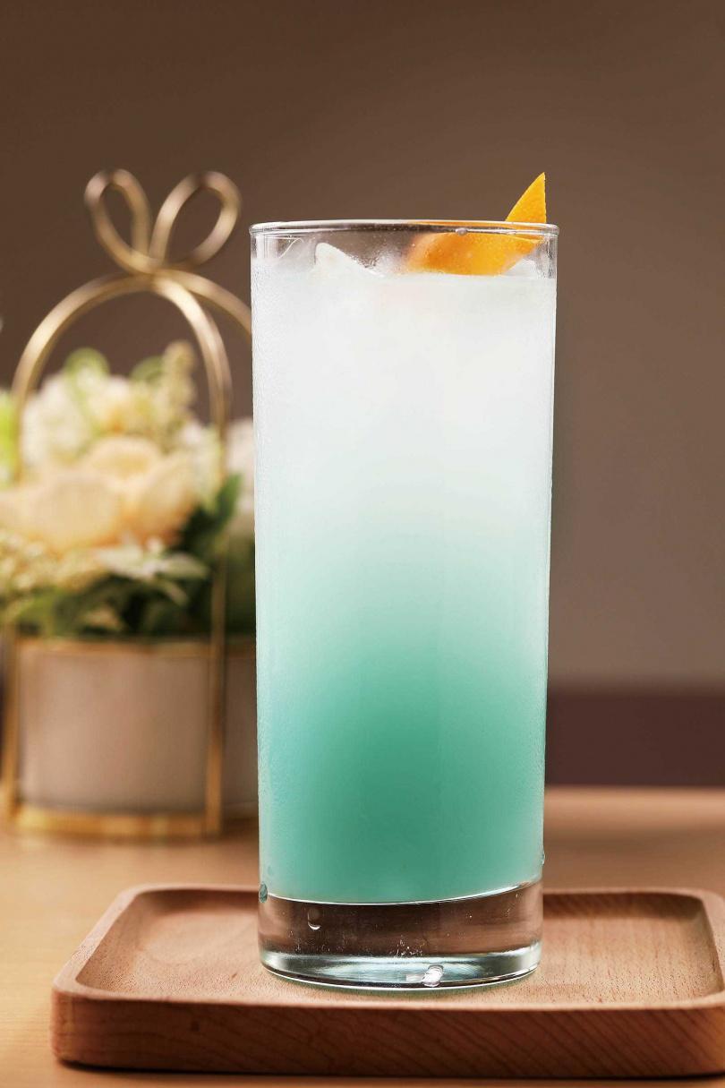 以藍柑橘糖漿、可爾必思、氣泡水製出藍白漸層的「可爾必思氣泡飲」,沁涼消暑。(120元)(圖/于魯光攝)
