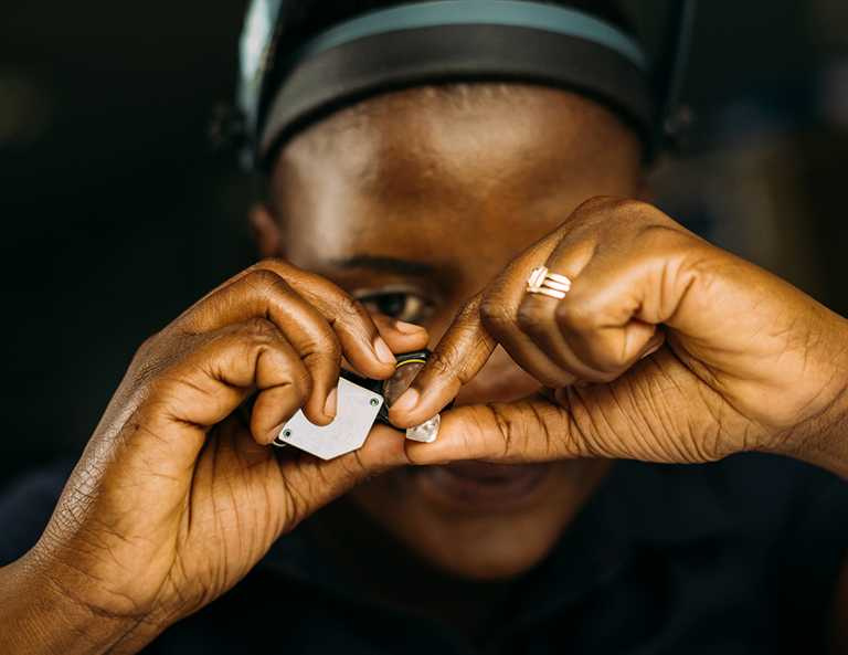 DE BEERS員工手持鑽石放大鏡,進行鑽石原石的分揀。(圖╱DE BEERS提供)