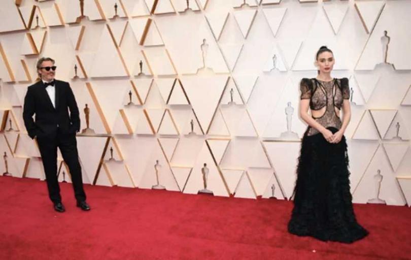 演出《小丑》的瓦昆菲尼克斯(Joaquin Phoenix)和女友魯妮瑪拉(Rooney Mara)相當恩愛,每每出席典禮,都可以看到瓦昆菲尼克斯如此癡情看著女友拍照的模樣,兩人是在拍攝《雲端情人Her》相識定情的。(圖/翻攝自Twitter)