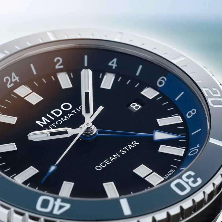 MIDO「Ocean Star GMT海洋之星兩地時區腕錶」藍色噴漆的第二時區指針,亦飾有白色夜光塗層。(圖╱MIDO提供)