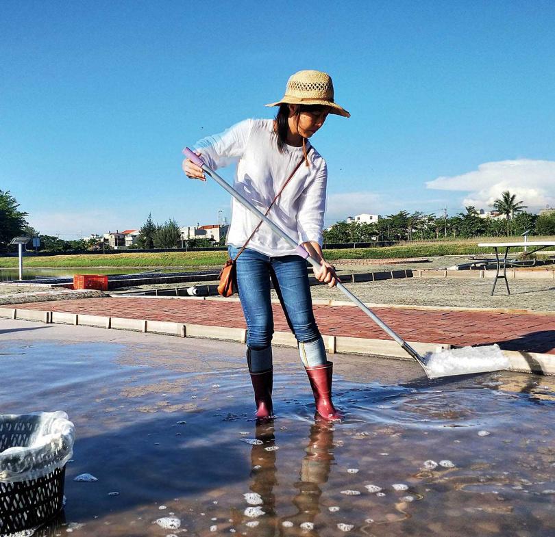 民眾體驗曬鹽過程中,撈完表層鹽花後,沉底的便是粗鹽,要用竹箕鏟起堆疊曬乾。(圖/高靜玉攝)