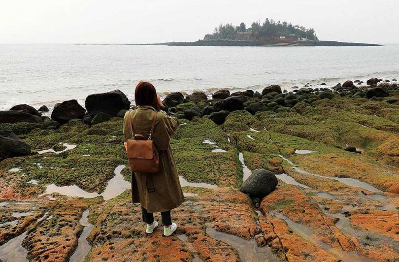 站在長年經海浪侵蝕出的綠石槽,正對面即是復興嶼。(圖/于魯光攝)