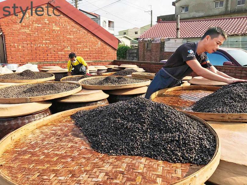 「新芳園醬油」第二代王福進(後)、第三代王榮生忙著洗掉豆子外層麴菌,可適度減少釀造時的麴味。(圖/品牌提供)