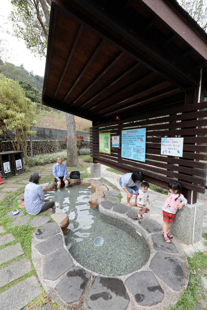 「谷關溫泉文化館」旁的公園區設有「溫泉魚去角質溫泉池」,不少人帶著一家大小來泡腳。(圖/于魯光攝)
