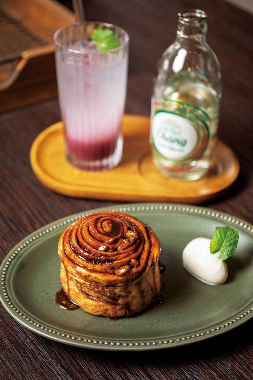 內裡扎實的「黑糖鹽肉桂卷」,包裹著烤香的核桃,搭配微酸氣泡飲「野莓蘇打」,能平衡味蕾。(黑糖鹽肉桂卷一○○元/份,野莓蘇打一二○元/杯)(圖/宋岱融攝)