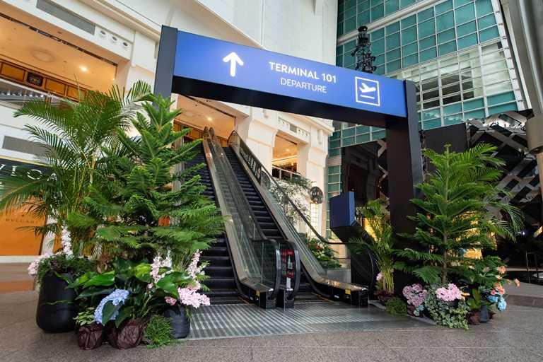 台北101購物中心4樓都會廣場往5樓的手扶梯,設置仿航廈閘口的大型裝置,讓人有「微出國」的身歷其境感受。(圖╱台北101提供)