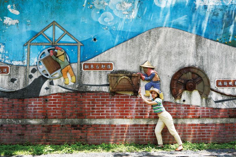 「和興炭坑」園區有一面陶板彩繪壁畫《煤的一生》,不但具有教育意義,遊客也能在此拍出逗趣照片。(圖/于魯光攝)