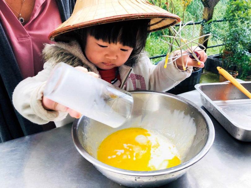 小朋友在大人的陪伴下,親手製作雞蛋糕。(圖/遠足生態農場提供)