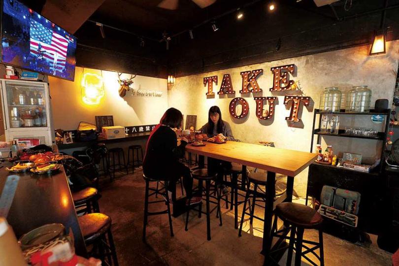 「Take Out Burger & Café」的裝潢走工業風,高掛的電視不時播放旅遊生活節目或球類比賽。(圖/于魯光攝)