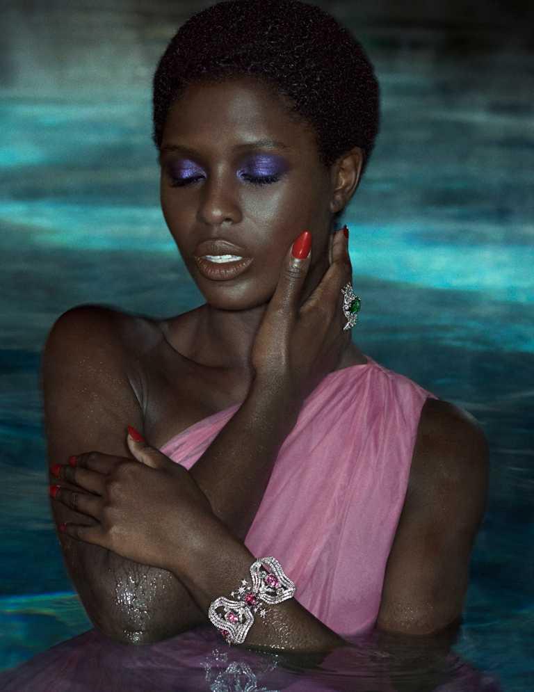 茱蒂透納史密斯(Jodie Turner-Smith)化身池中繆思女神,佩戴GUCCI「Hortus Deliciarum歡愉花園」系列藍寶石白金鑲鑽戒指、紅色尖晶石白金鑲鑽手鐲等高級珠寶,展現醉人詩意。(圖╱GUCCI提供)