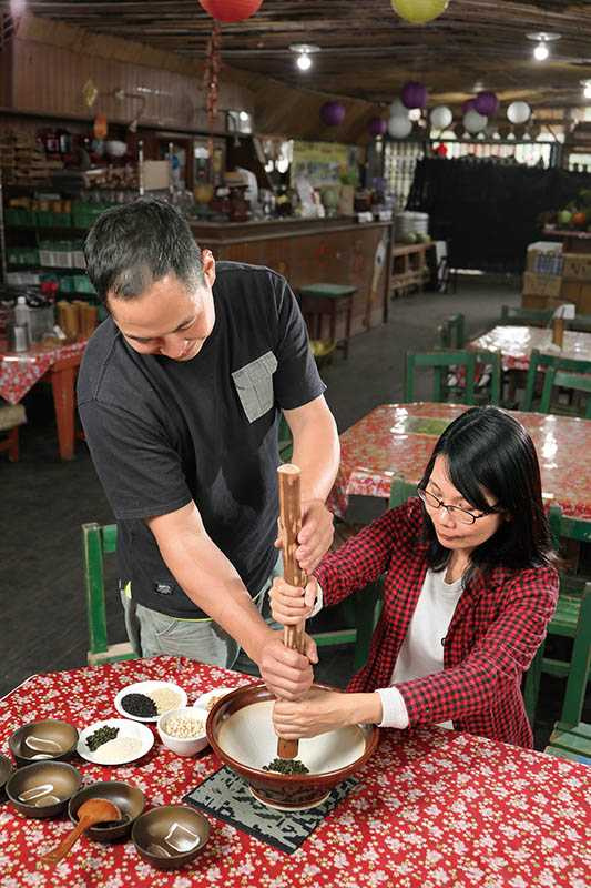 在「十二寮休閒農園」可體驗客家擂茶,將綠茶葉、米麩與芝麻等5、6種材料倒入大缽,再搗成粉。(攝影/于魯光)