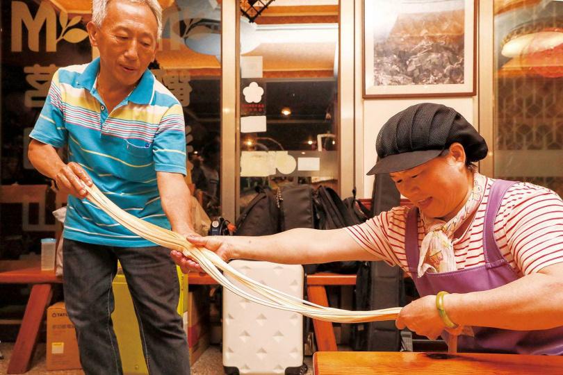 「茗園茶葉民宿」老闆夫妻檔,合力將糖膏愈拉愈長。(圖/焦正德攝)