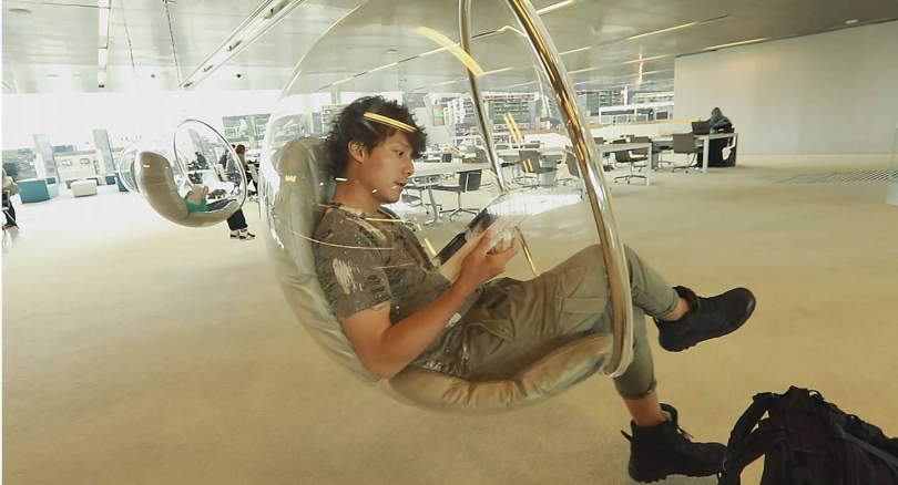 進入卡達杜哈國家圖書館的廖科溢,坐上館內的玻璃球型懸吊椅。(圖/亞洲旅遊台提供)