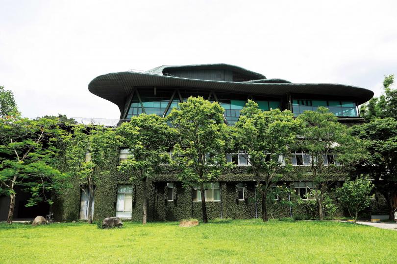 「雲門劇場」下層建築是「中央廣播電台」淡水分台舊址,上層為具有浮雲意象的銅綠屋頂,與綠色玻璃帷幕一同呼應周遭林景。(圖/于魯光攝)