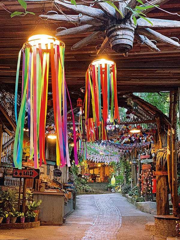 Baan Hom Tien入口以蠟燭壁畫與繽紛彩帶布置,營造出如同時空隧道的懷舊氛圍。(圖/官其蓁攝影)